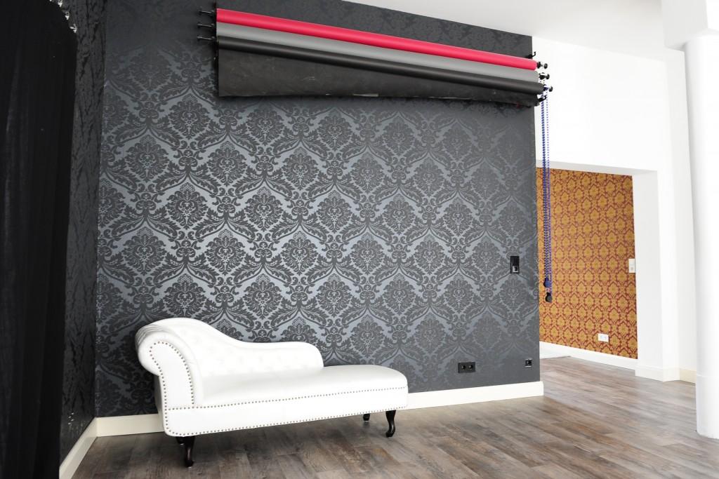Weißes Sofa vor schwarzem Tapetenhintergrund