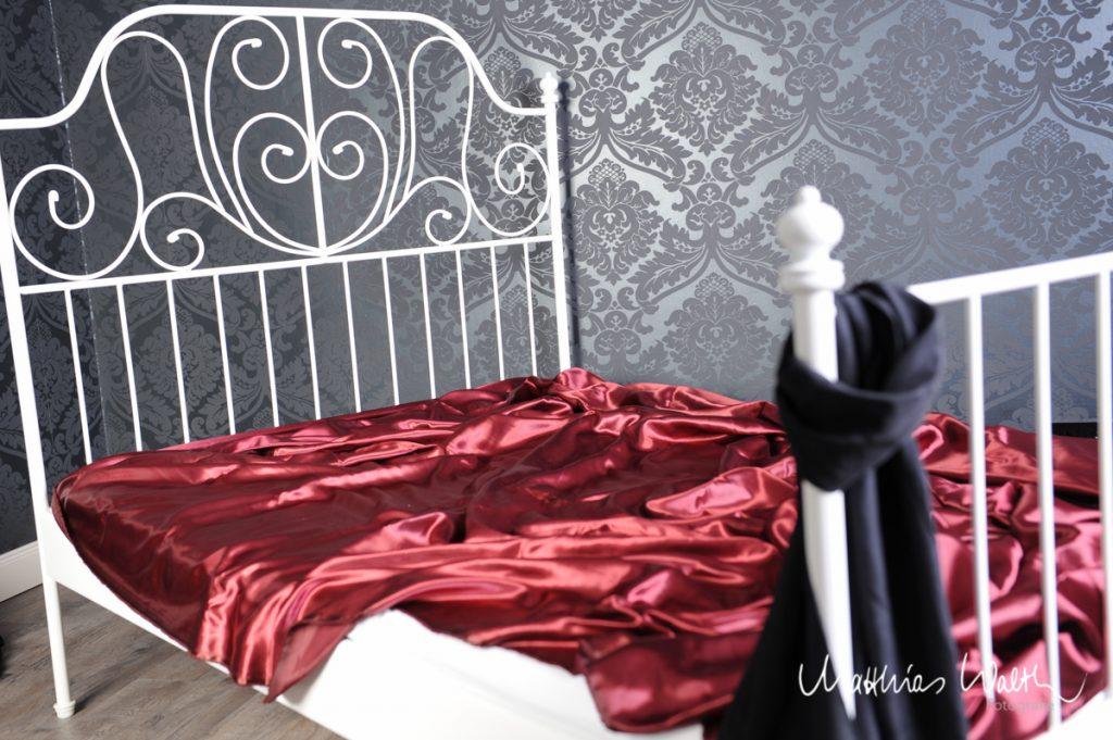 Roter Satinstoff auf weißem Bett im Fotostudio